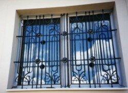 решетка с орнаментом на окне в частном доме